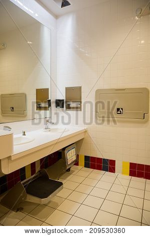 Friendly bathroom for children with low level sink and special step stand for little children. Comfortable restroom for children.