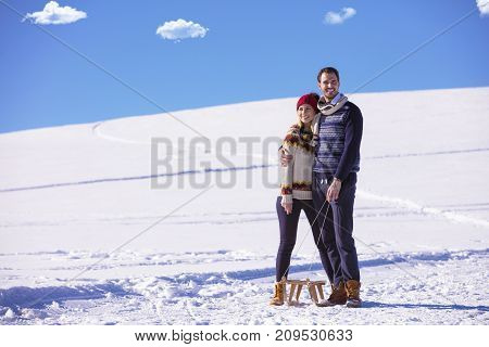 Young playful couple having fun sledging down snow covered hill.