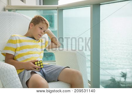 Miami USA October 03 2017: Portrait of cute dreamy kid boy sitting on a balcony chair and holding Rubik's cube in his hands. Child playing with Rubik's cube. Lifestyle