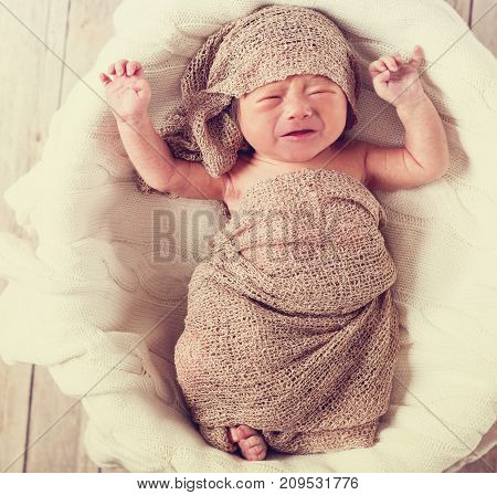 Crying little asian infant baby boy in a basket