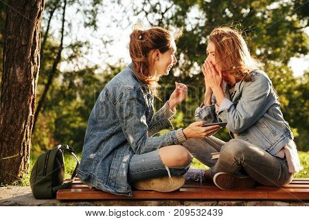 Two cheerful female friends sitting on wooden bench with crossed legs, talking while holding smartphone in park