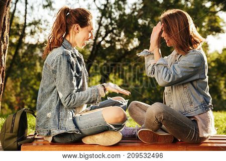 Two pretty girls clap their hands while sitting on wooden bench in park outdoor