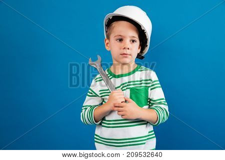 Bored young boy in protective helmet posing with wrench like engineer and looking away over blue background