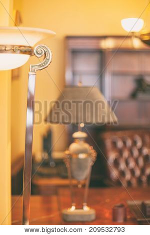 A lamp with a shade stands on a table on the background of a leather chair in a rich atmosphere