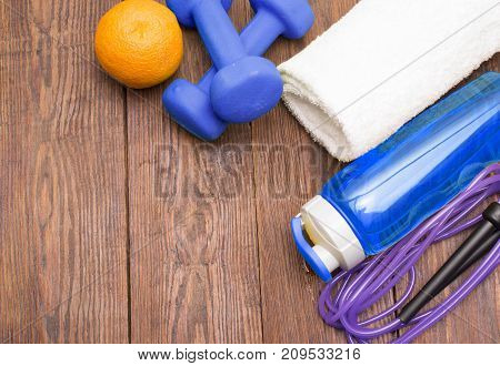 Fitness equipment. Healthy food. Sneakers, water, skipping rope and orange on wooden background. Fitness concept