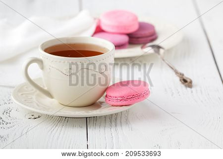 Macaroons With Hot Tea On Wooden Table.