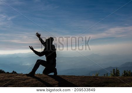 silhouette of a man who praying over the mountains landscape