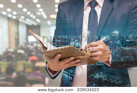 Double exposure of Businessman writing the note book on the Abstract blurred photo of conference hall or seminar room with attendee background, 3D illustration