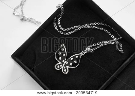 Black silver butterfly pendant in black jewel box closeup
