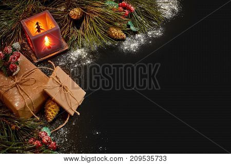 Christmas gifts and red candlestick near green spruce branch on a black background. Christmas background. Top view. Copy space. Still life. Flat lay. New year