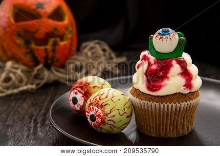 Halloween cupcake with blood monster eyes. Cupcake with halloween pumpkin. Halloween cake on dark wooden table. Close up