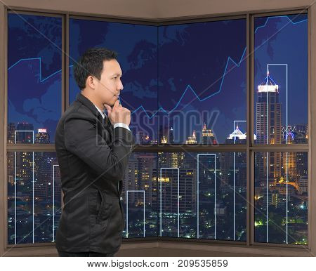 Businessman looking at Trading graph on the cityscape at night and world map backgroundBusiness financial concept