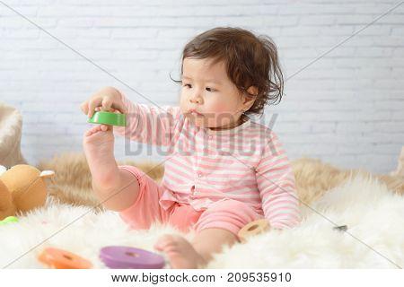 Sweet Beautiful baby girl playing on beautiful white furry.Newborn baby concept.