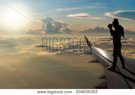 silhouette of photographer taking photo on airplane wing Challenge business concept