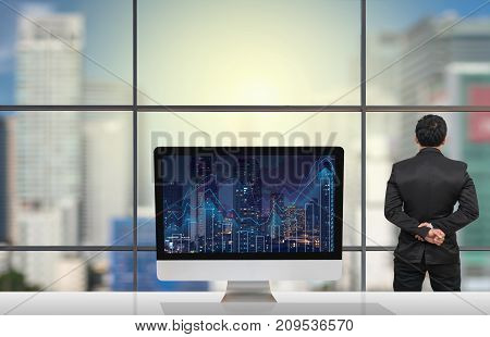 Back side of Businessman looking at citiy out off windows glass with Computer show Trading graph on the cityscape at night and world map background on the table in meeting roomBusiness financial concept