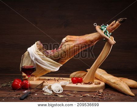 Example of serving with jamon, tomatoes and traditional bread. Serving with black pepper and onion rings. Whole Mediterranean jamon on a wooden stand with a knife lean on a table. Dark image with a wooden background and a wooden table.