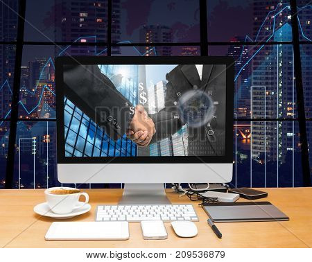 Workspace with computer desktop with Hand shake between businessman at the screen on the trading graph over the blurred photo of cityscape backgroundElements of this image furnished, 3D illustration