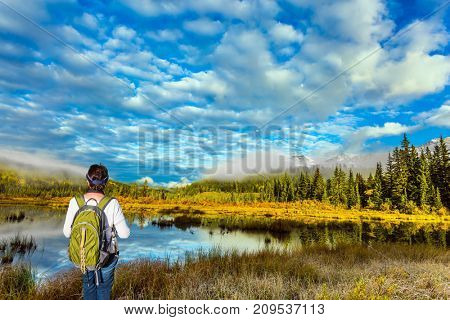 Elderly enthusiastic woman with a green backpack is standing by the lake. Cool autumn morning in the Rocky Mountains. The concept of ecological tourism