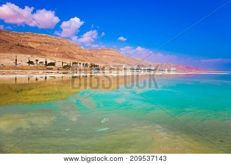 Midday heat evaporates water. Turquoise water of the Dead Sea, Israel. Between the sea and dry mountains of red sandstone highway passes. The concept of medical and ecological tourism