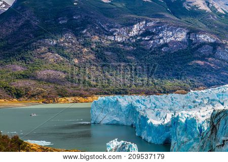 The glacier shine with reflected sunlight. The concept of exotic and extreme tourism. The fantastic glacier Perito Moreno, in the lake Argentino, Patagonia