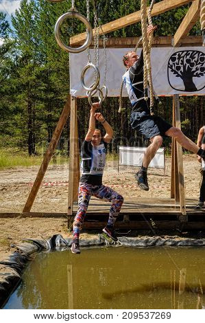 The Girl Climbs On Rings Over Water. Heros Race