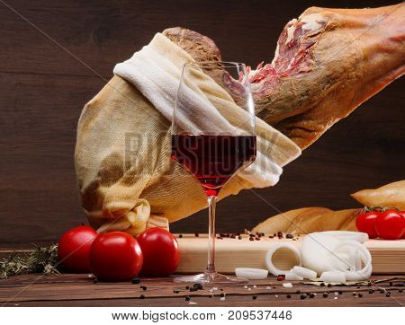 Iberian ham pata negra from Spain, tomatoes, onion rings and red wine glass. Horizontal Closeup image. Whole Mediterranean traditional jamon on a wooden stand