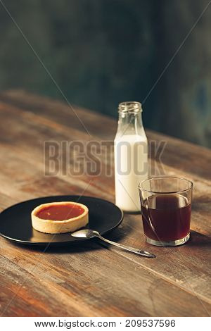 The cake and cup of coffee and bottle of milk on wooden table