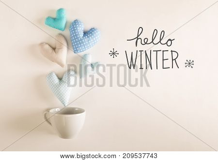 Hello Winter message with blue heart cushions coming out of a coffee cup
