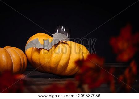yellow pumpkin lies on a black background with a candle and a drawing of a bat