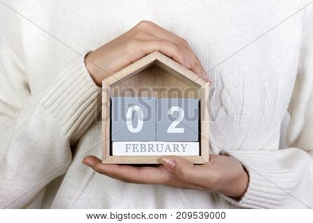 February 2 in the calendar. the girl is holding a wooden calendar. Groundhog Day World Wetlands Day.