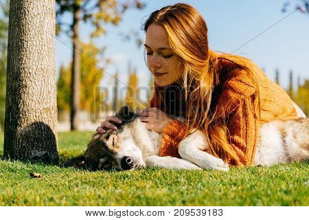 a young active girl walks with her big dog in the park, lies on a green grass