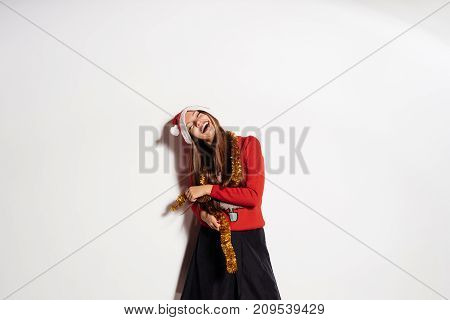 young cheerful happy girl celebrates New Year and Christmas, in a warm red sweater and gold tinsel