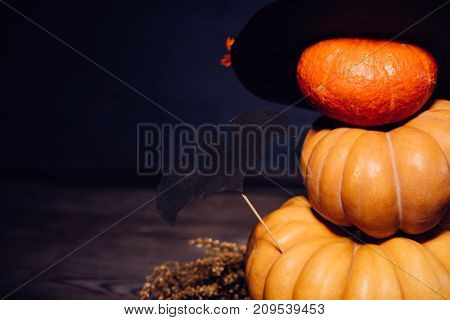 composition for decorating a house for halloween, yellow and orange pumpkins, a big black witch hat