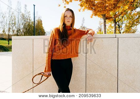 young active girl walking with her big dog in the park posing by the white fence