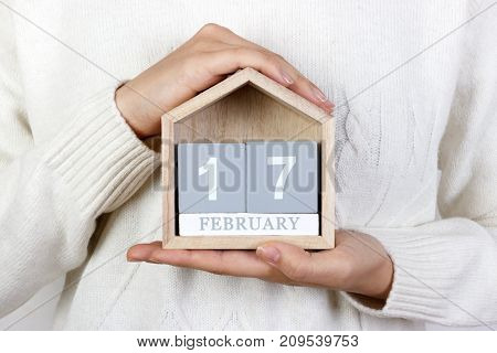 February 17 in the calendar. the girl is holding a wooden calendar. Random Acts of Kindness Day.