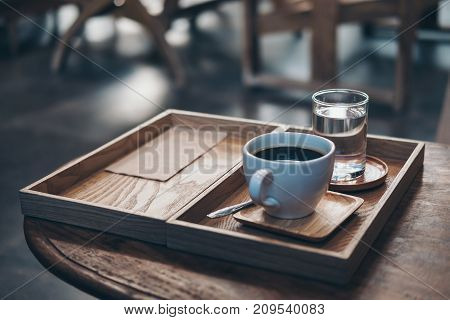 Closeup image of a cup of hot coffee and a glass of water in vintage wooden tray on the table in cafe