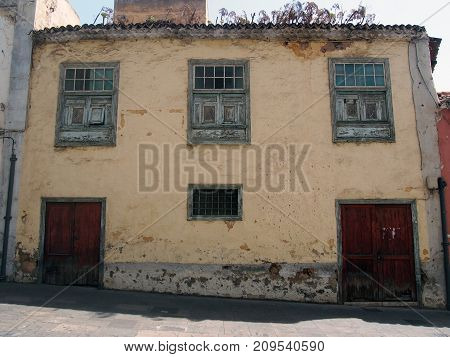 typical Spanish old house in tenerife with yellow plaster walls and weeds growing from the roof fading green windows on a sloping street