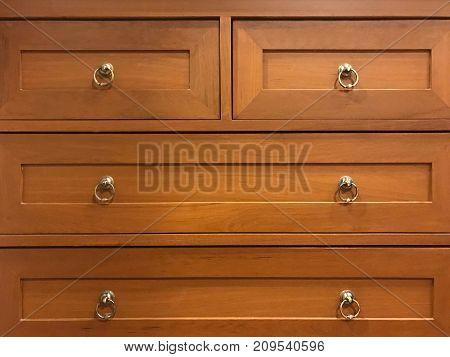 Wooden drawer cabinet with brass handle under warm light