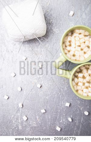 White Knitting Ball And Needles In Two Cup Of Coffee With Marshmallow On Grey Background. Top View.