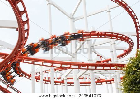 Roller coaster rail loop with motion blur player over cloudy sky