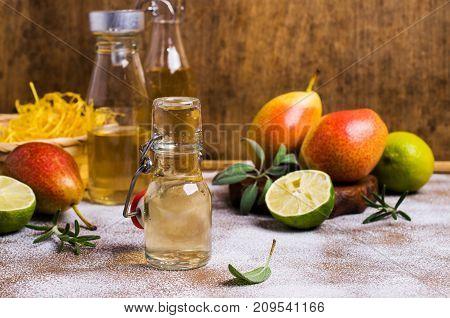 Homemade fruit vinegar on rustic wooden background. Selective focus.