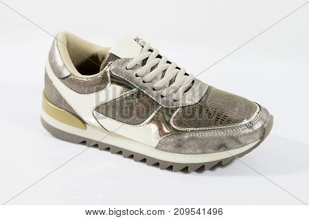 Female brown sneaker on white background, isolated product.