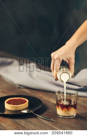 The female hand with milk and cake and cup of coffee on wooden table