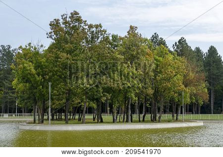 Popular  North park  for rest with autumnal old forest, wooden bench and lake in  Vrabnitsa district, Sofia, Bulgaria