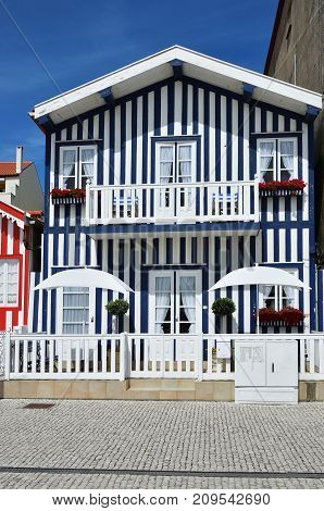 Costa Nova Portugal -June 10 2017:  Blue striped house in the famous resort on the Atlantic coast Portugal. Popular tourist destination to spend vacation time