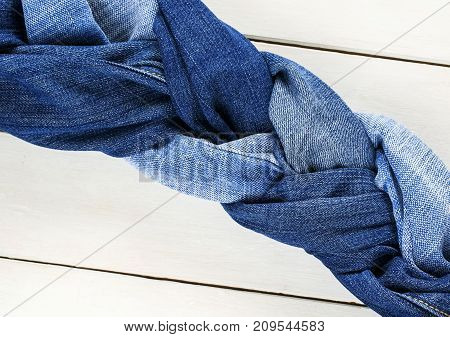 stylish and twisted braid woven from a variety of blue jeans on white wooden table