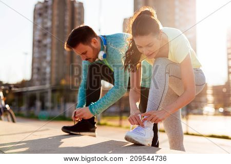 Runners tying their running shoes and getting ready for long run