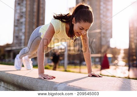 Picture of young woman doing push ups in urban area