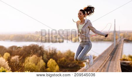Active young woman jumping with skipping rope outdoors