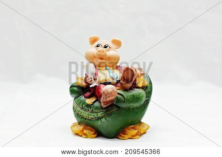 Souvenir piggy bank for coins in the form of a sitting piglet isolated on white background.